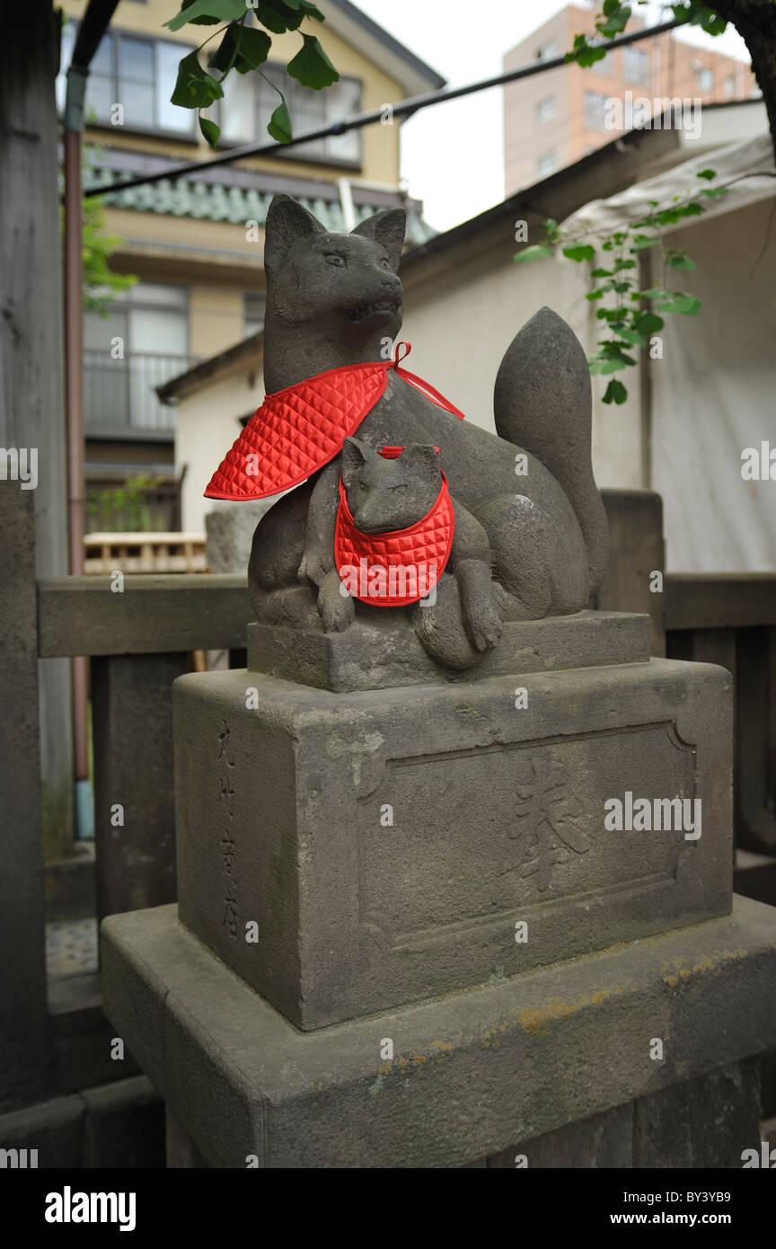 Fox statue Inari decorated with red bibs, Sanja Matsuri, Asakusa, Tokyo, Japan - Stock Image