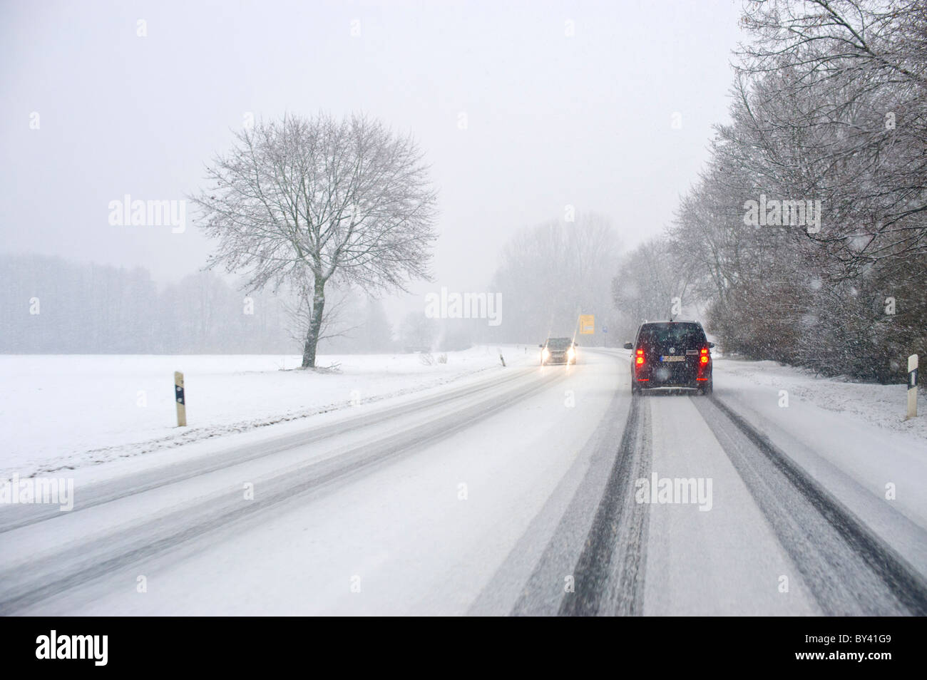 street conditions winter wintertime street seen out of a car window carwindow snow snowing street road ice icy covered - Stock Image