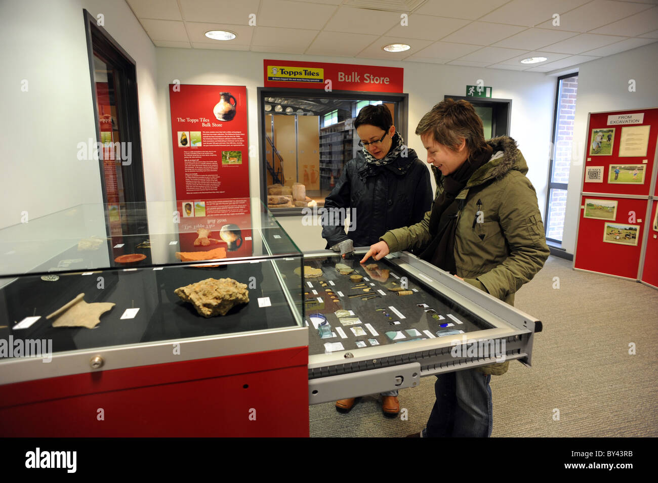 People looking through the finds inside the Collections Discovery Centre at Fishbourne Roman Palace - Stock Image