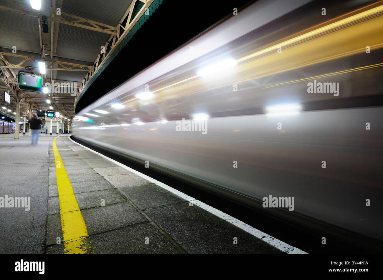 High speed train passing through a almost deserted railway station platform at night creating streaks of light. - Stock Image