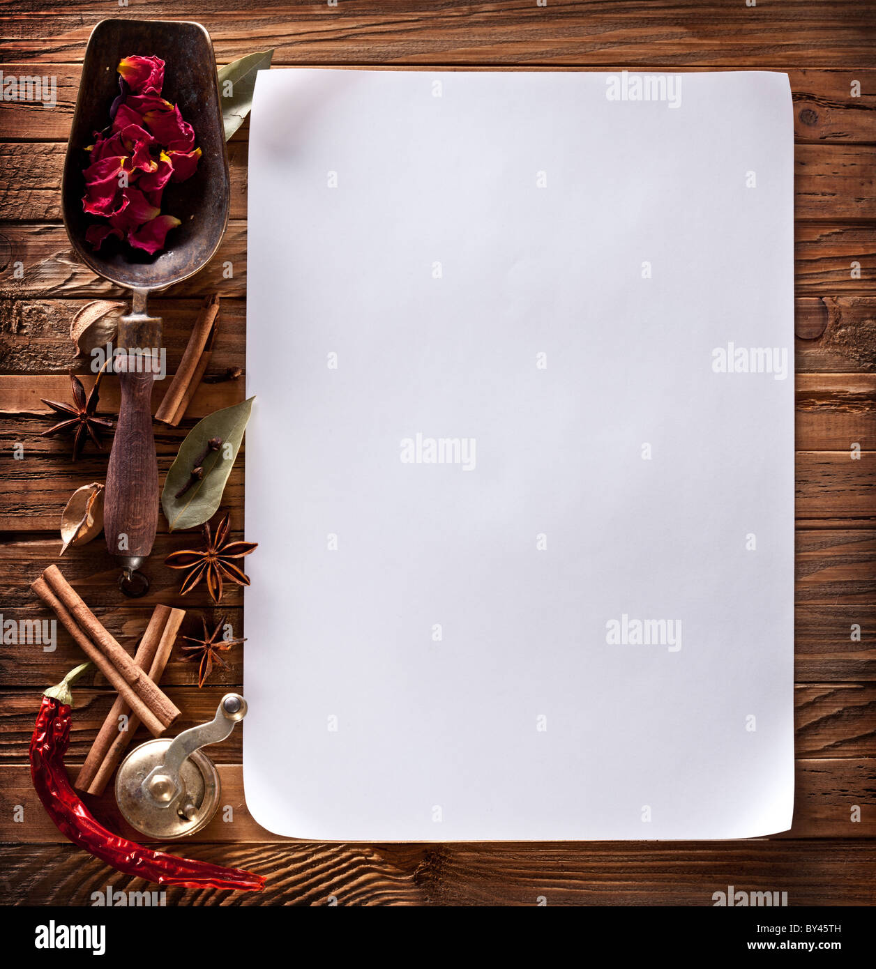 Image of white paper with spices on a wooden surface Stock Photo