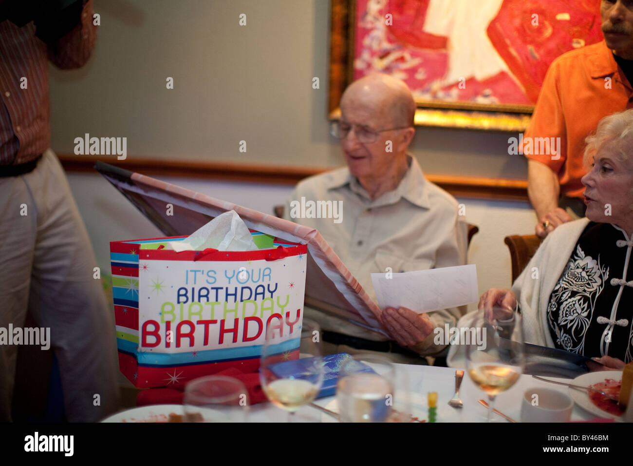 90 Year Old Anglo Male Looks At Gift During His Birthday Party A Restaurant In Austin Texas USA