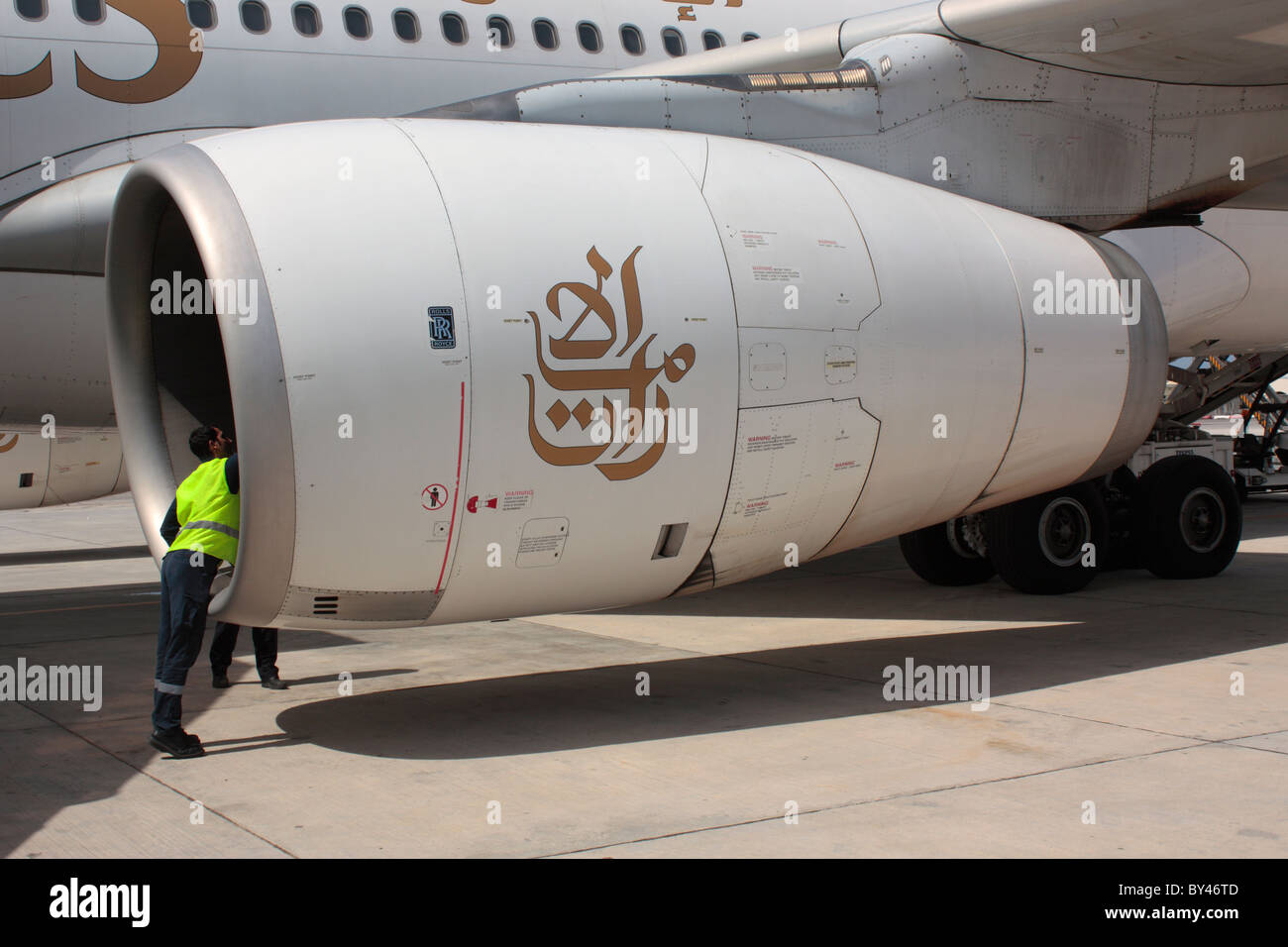 Airport employee inspecting a Rolls-Royce Trent 700 jet engine on an Emirates Airbus A330-200 - Stock Image