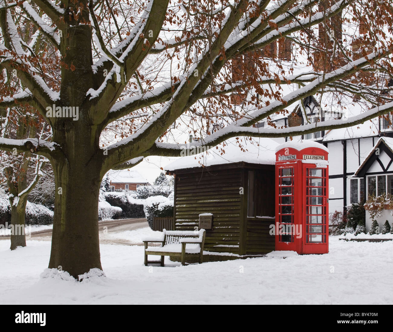 Red telephone box with snow on English village green - Stock Image