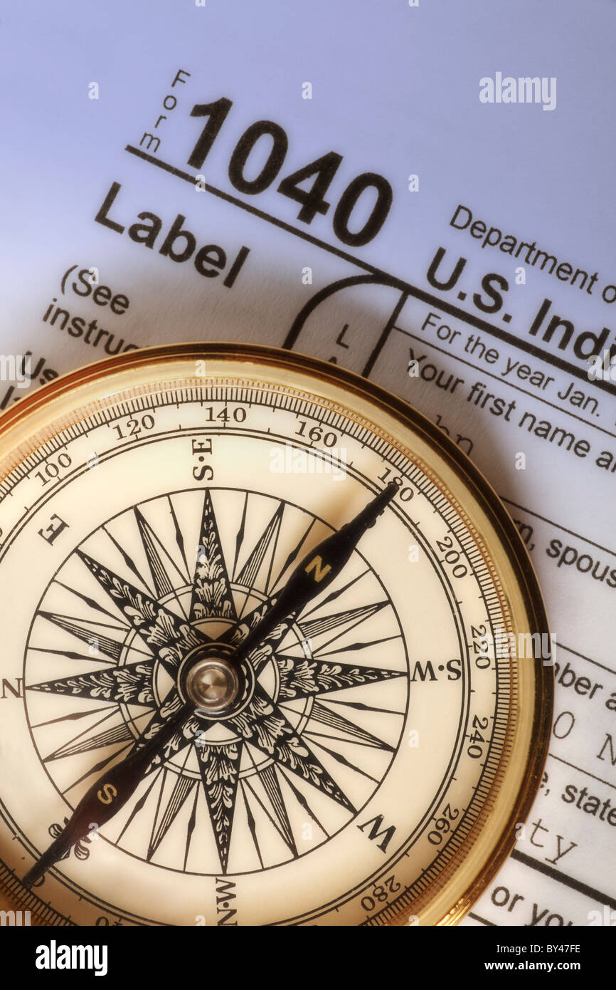 Compass on a Federal Income Tax 1040 form illustrating the concept of income tax preparation and guidance - Stock Image