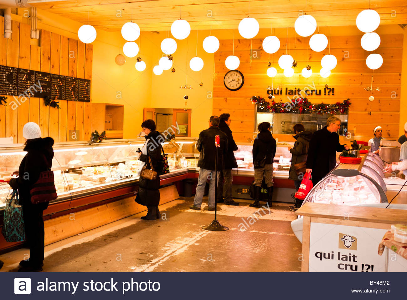 MONTREAL, Canada - Customers in a modern fromagerie at the the Jean-Talon Market in Montreal, Canada. - Stock Image