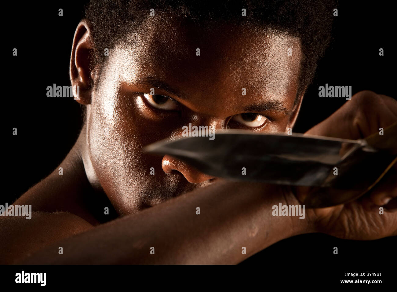 Young black male model posing with a knife
