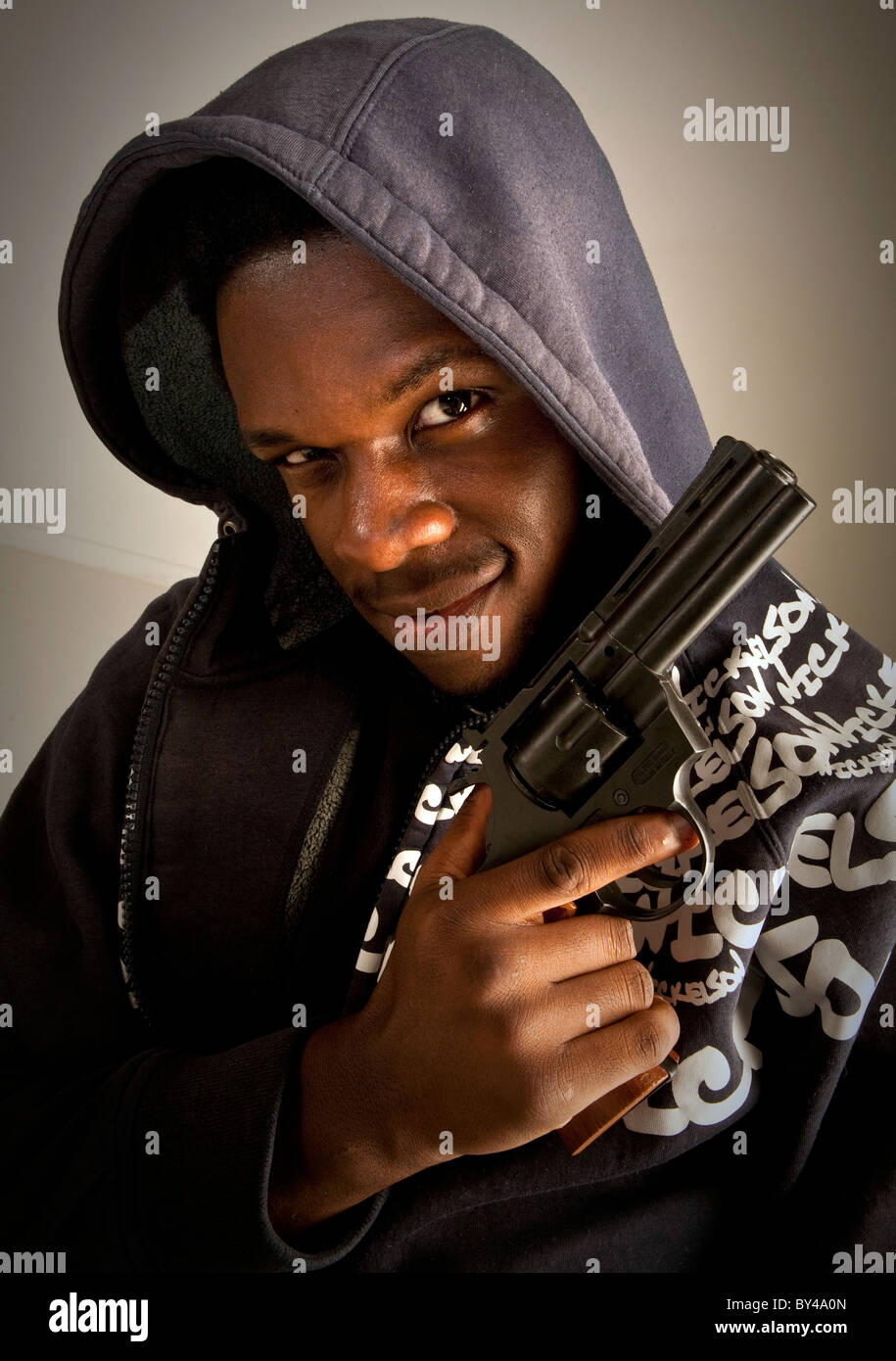 Young black male model posing with a gun