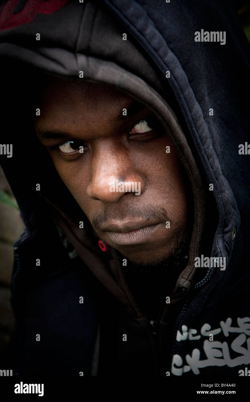 Young black model wearing a hoody and looking menacing - Stock Image