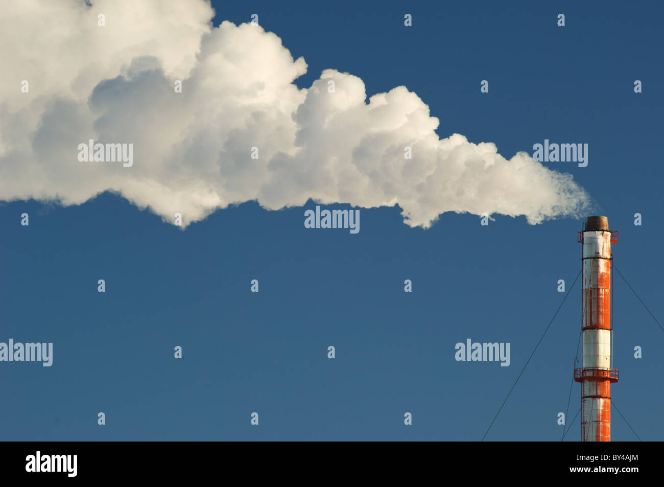 Smoke, gas and steam billows from a smokestack against a blue sky. - Stock Image