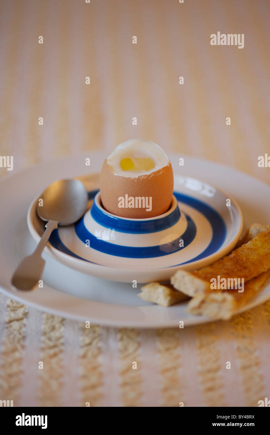 Boiled egg in egg cup with tea spoon and buttered soldiers Stock Photo
