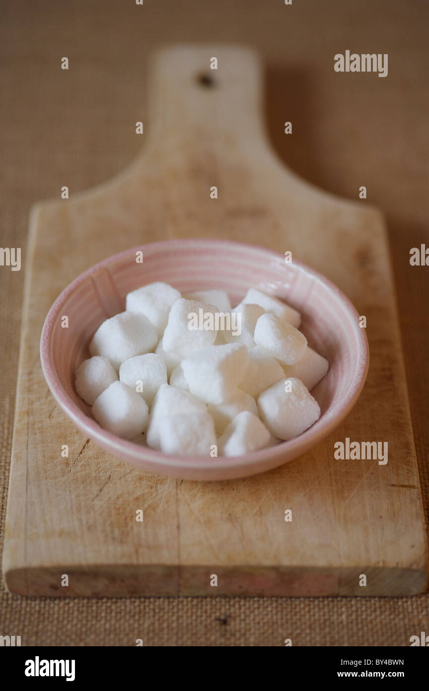 Sugar lumps in bowl on wooden serving board - Stock Image