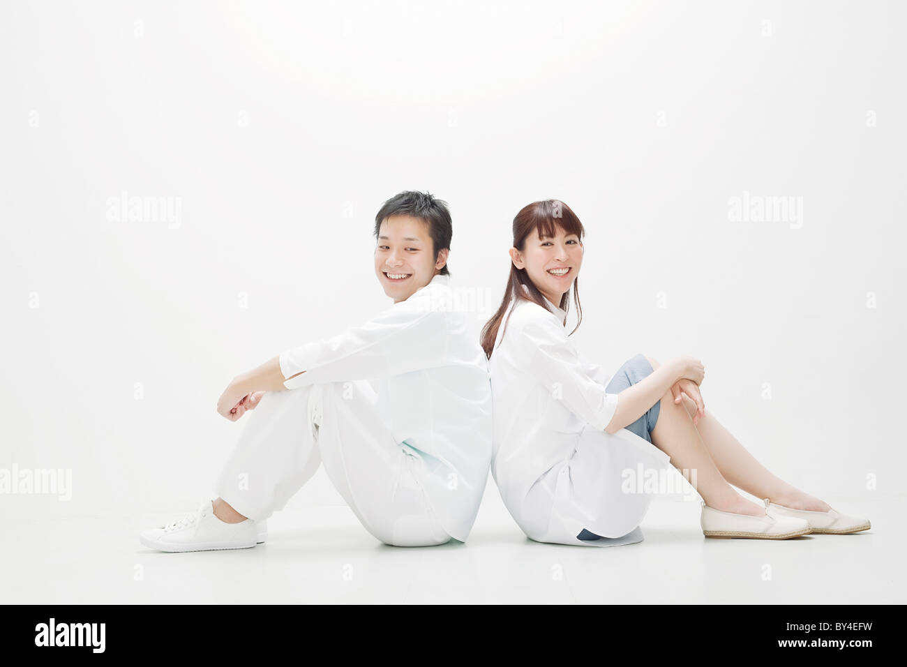 Young couple sitting back to back Stock Photo
