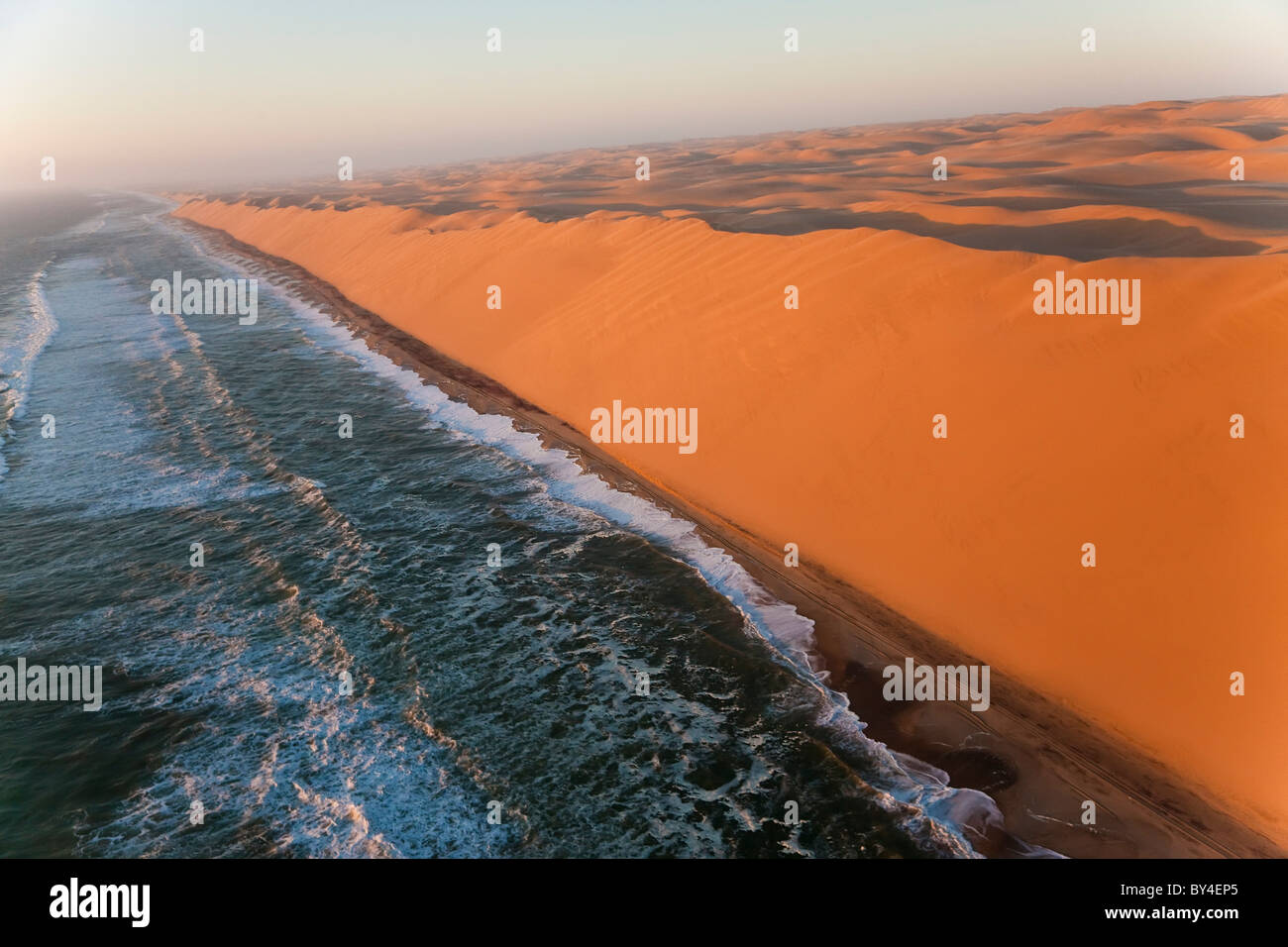 Aerial view over sand dunes & sea, Namib Desert, Namibia - Stock Image
