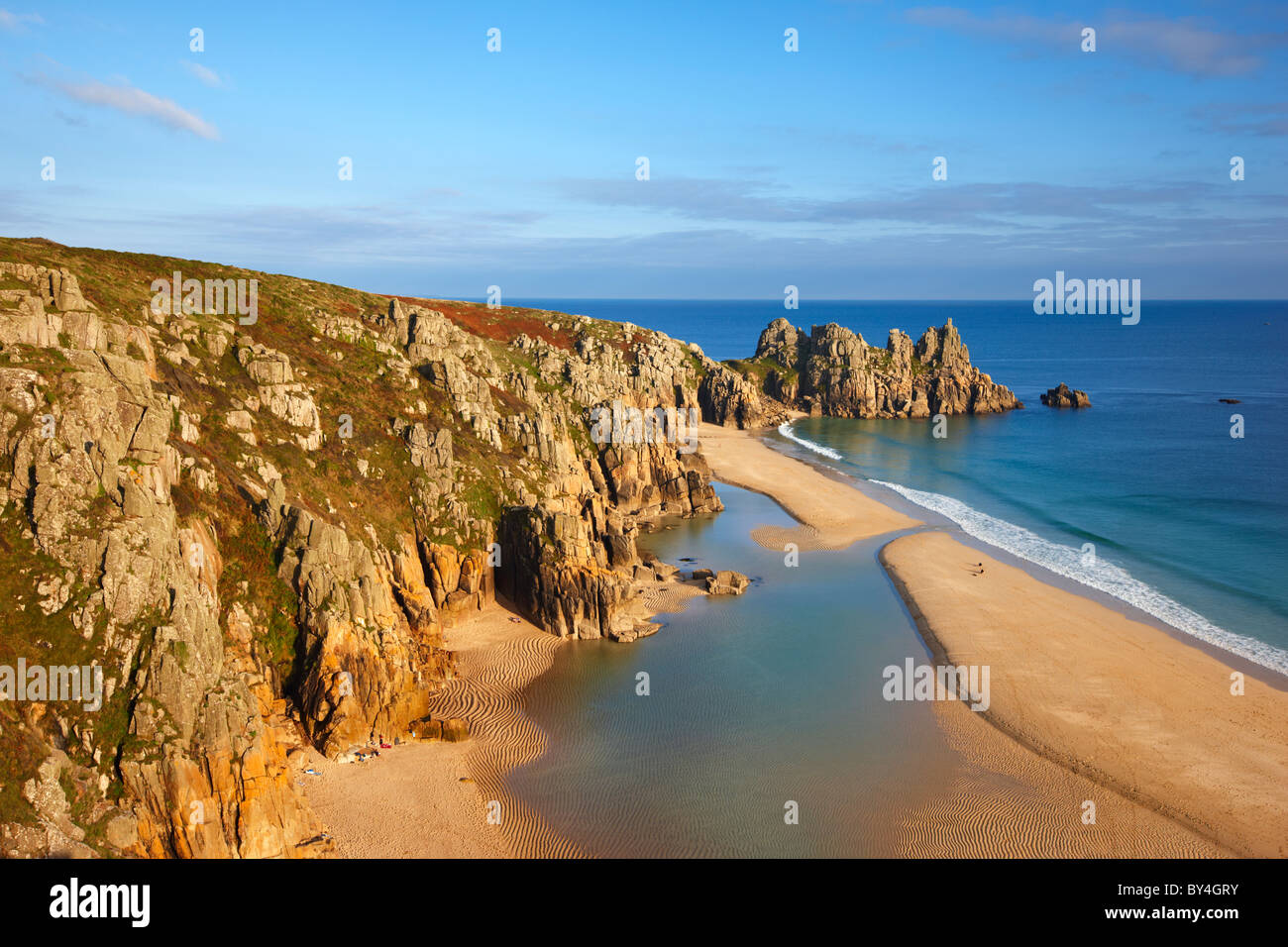 Large tidal pool covers the beach as the evening sun filters through bathing Logan Rock in warm sunshine, Porthcurno - Stock Image
