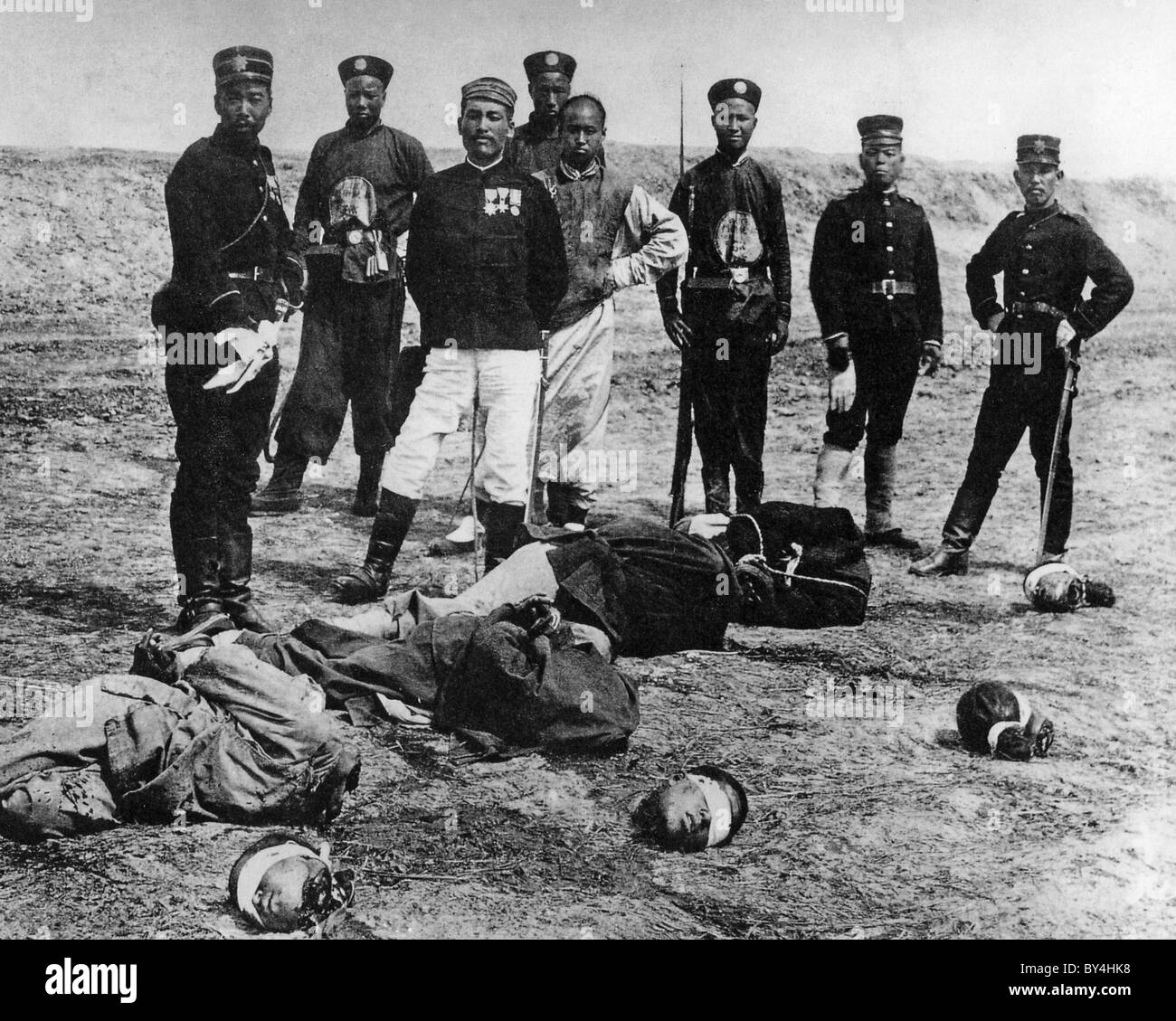 BOXER REBELLION Chinese executioners  with their victims in a 1900 photo with Japanese soldiers in the background - Stock Image