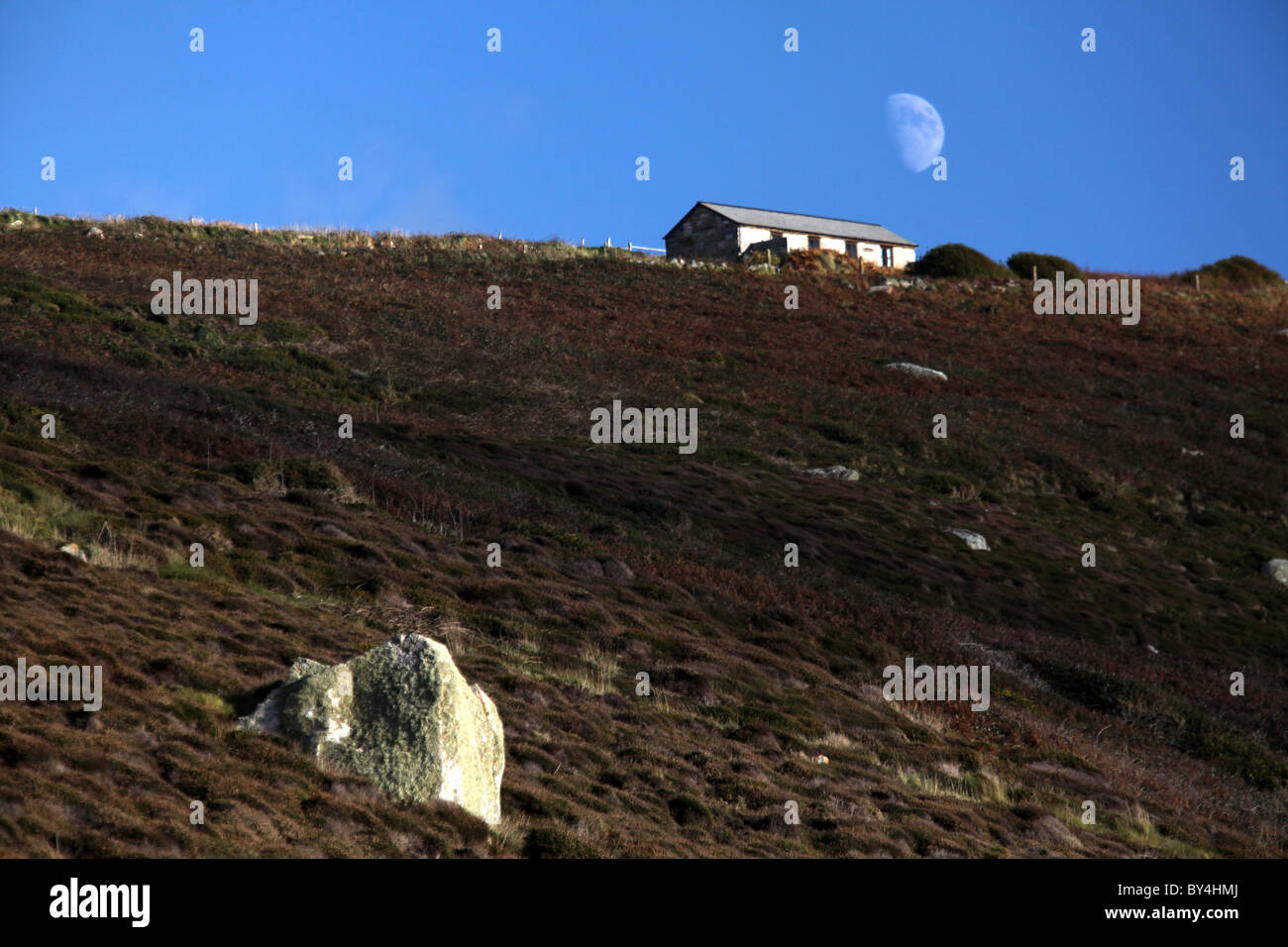 A solitary house with a moon above near Nanjulian in Penwith, Cornwall, England. - Stock Image