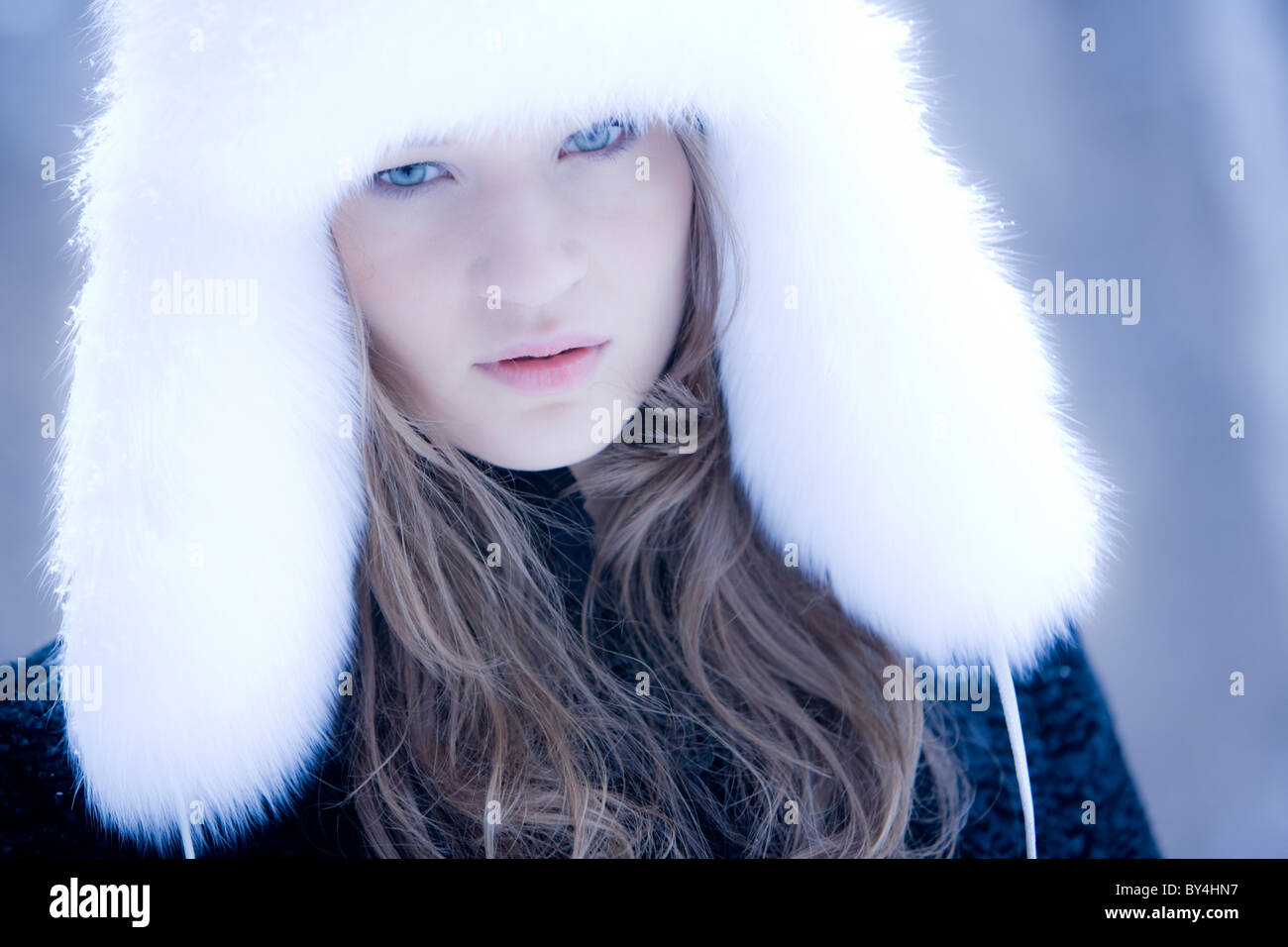 Portrait of attractive young woman wearing white fur cap looking at camera Stock Photo