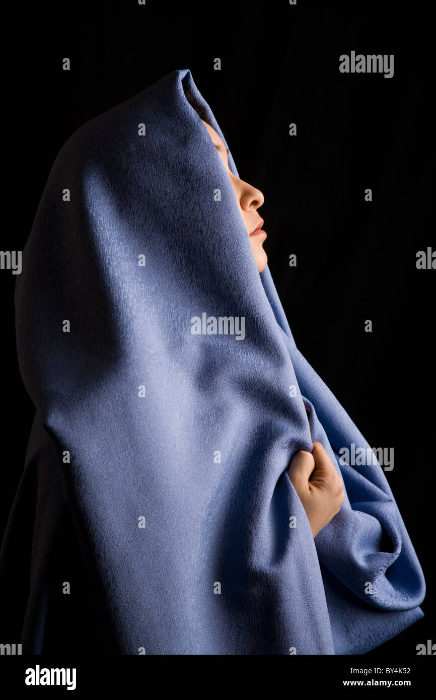Image of moslem woman with blue fabric on her head - Stock Image