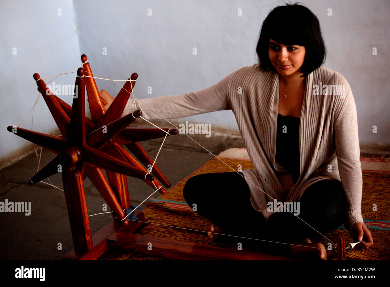A girl using spinning wheel to make thread Stock Photo
