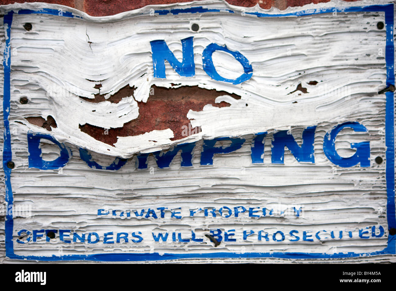 a no dumping sign that has been set on fire and melted during an act of vandalism - Stock Image