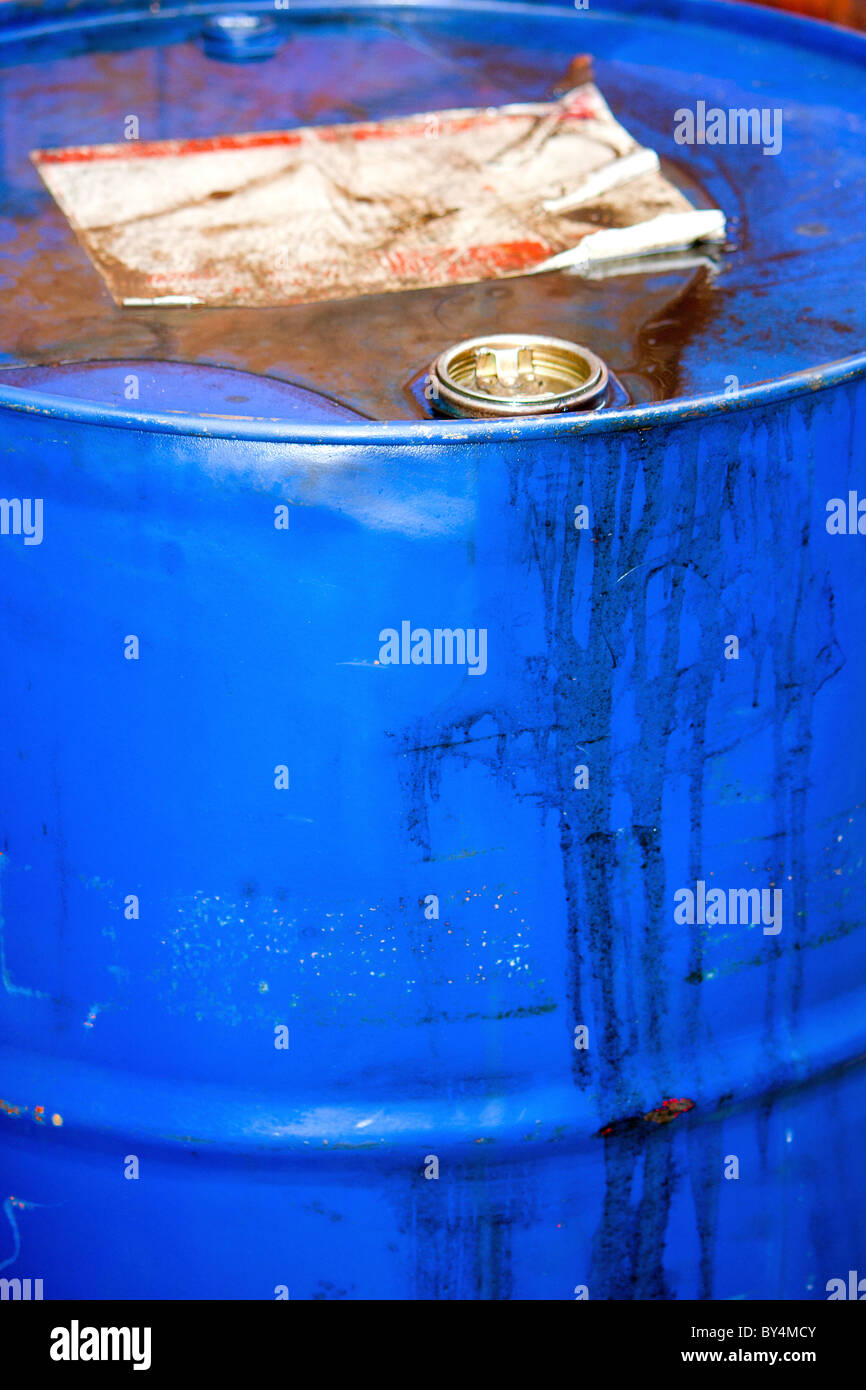 A dumped blue rusted corroded metal drum filled with unknown hazardous chemicals or toxic waste - Stock Image