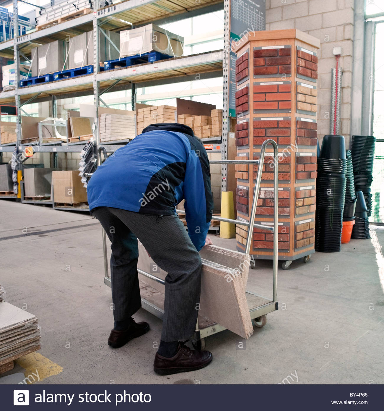 Man loading sheets of chipboard wood on to a shopping trolley in the building section of a B&Q warehouse store, - Stock Image