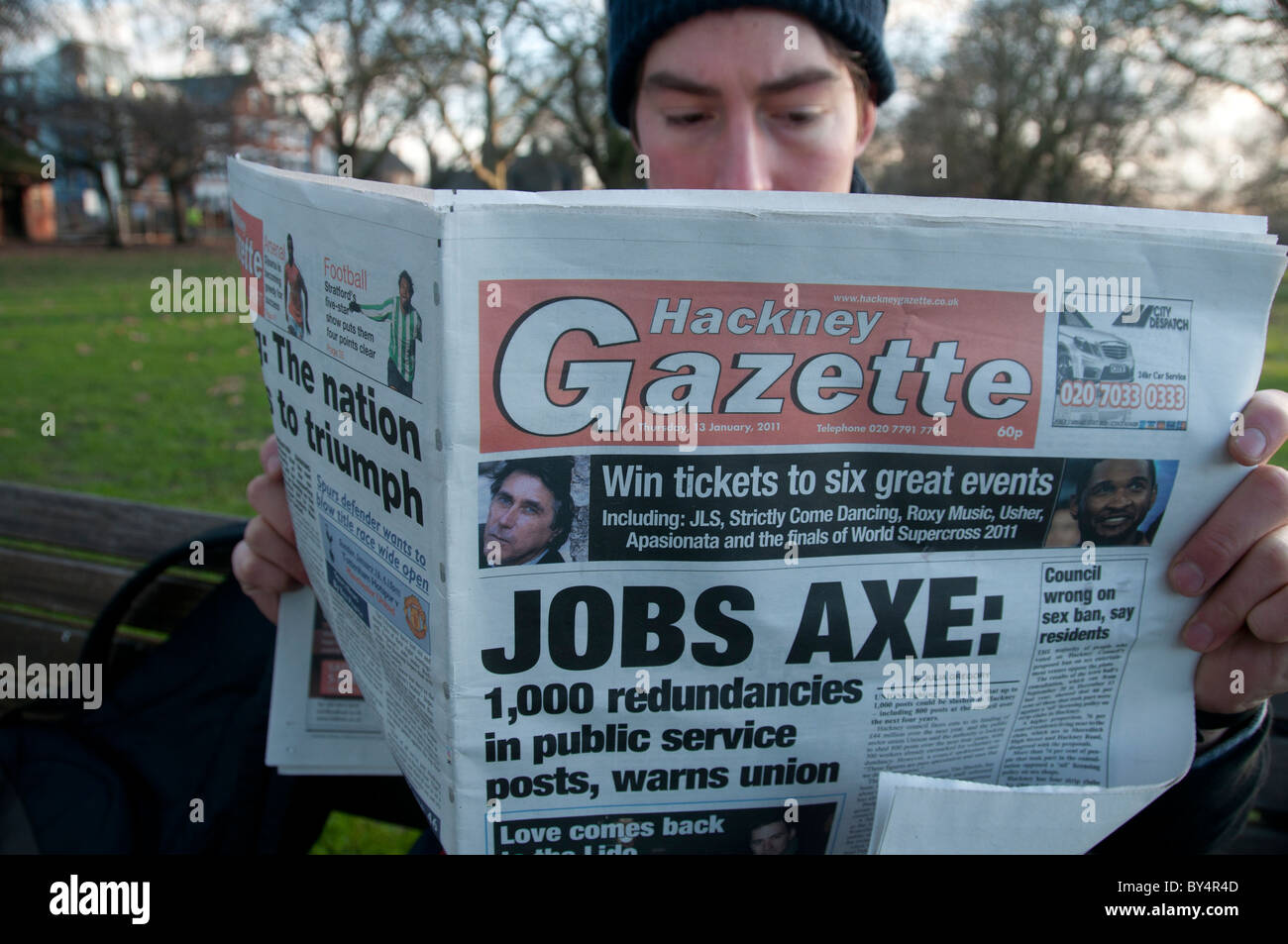 Hackney economic crisis.Young man reading Hackney Gazette with front page with headline Jobs axe - Stock Image