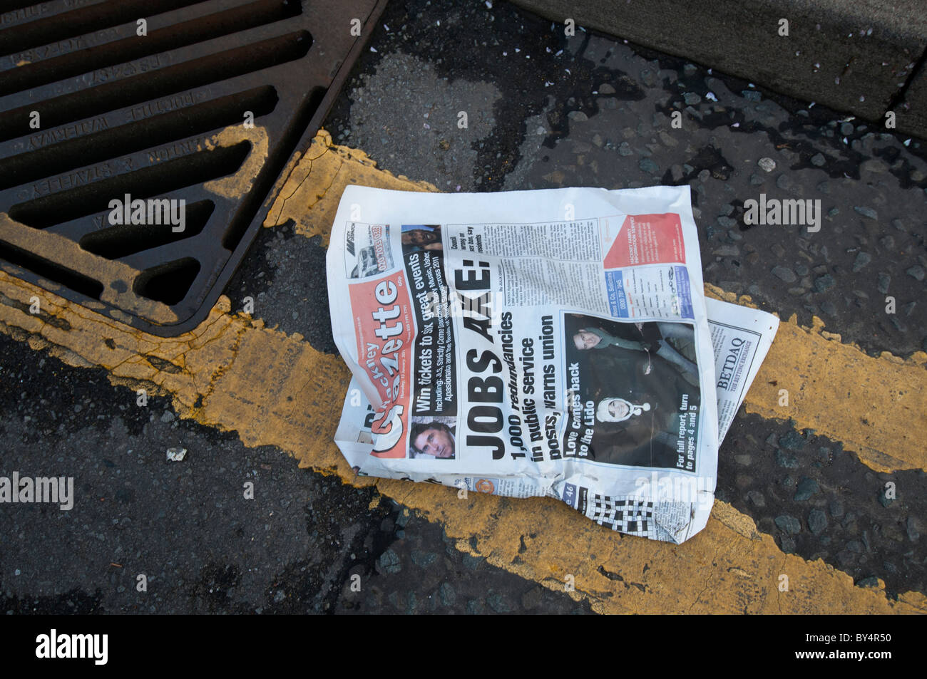 Hackney economic crisis. Newspaper with front page headline ' Jobs axe' in the gutter - Stock Image