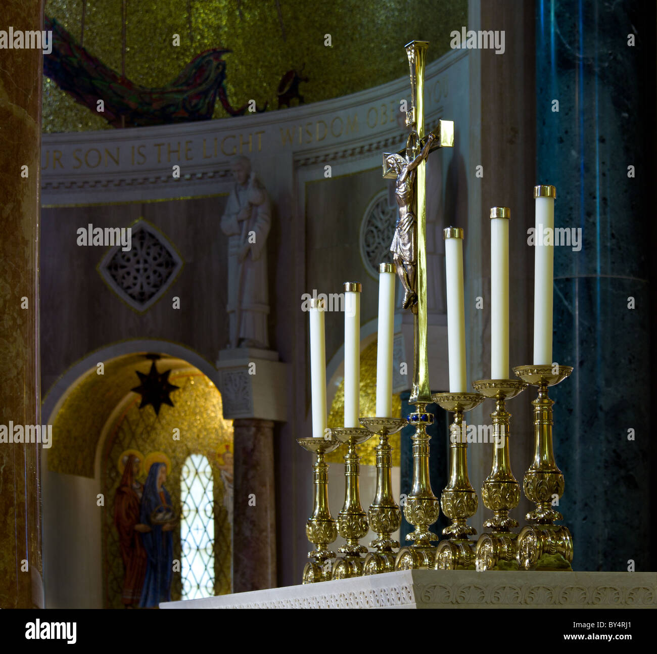 Set of ornate carved candlesticks on altar illuminated by sunlight with the darker alcoves of the church behind Stock Photo