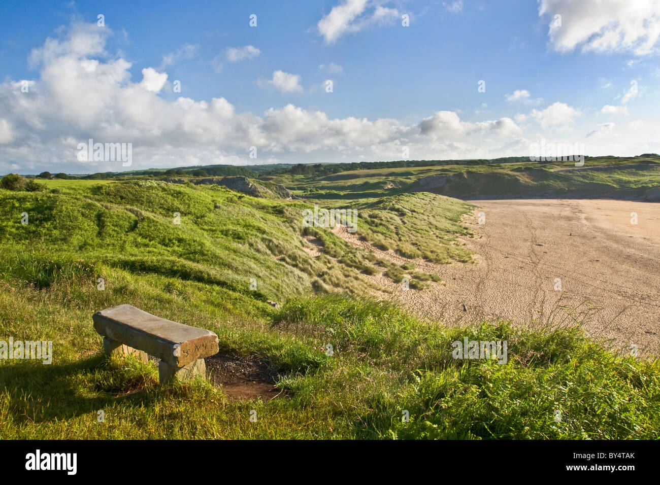 Stone seat overlooking sand dunes and beach at Broad Haven South, Pembrokeshire. Very early morning. - Stock Image