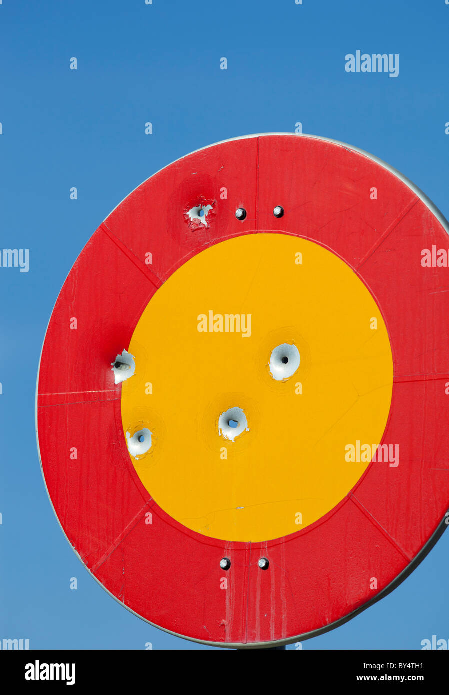 Bullet holes on round colorful traffic sign - Stock Image
