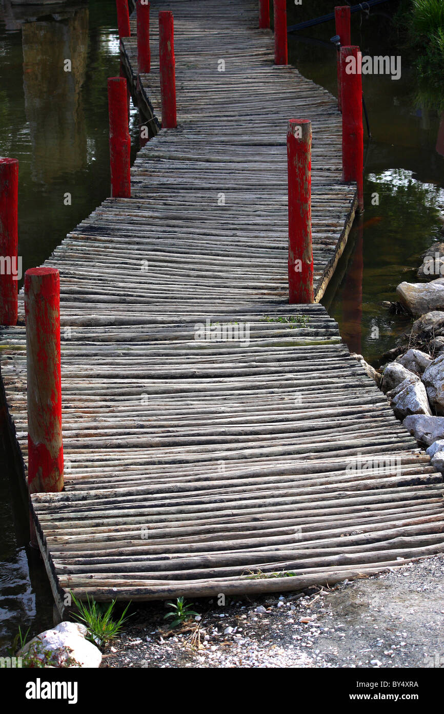 A wooden rickety bridge over a large pond or small lake full of water - Stock Image