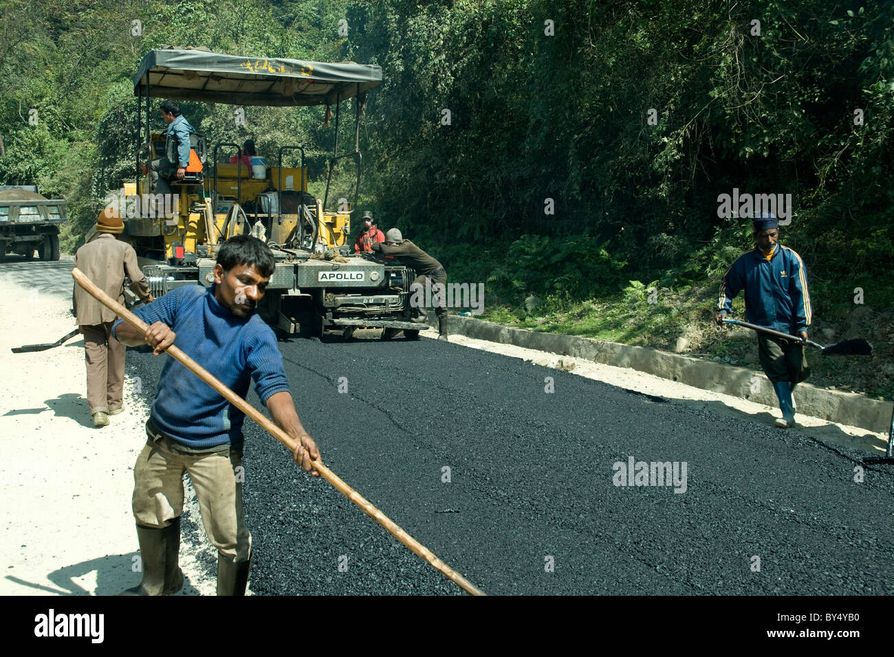 In mountainous Bhutan the road network and surfaces are constantly repaired and extended - Stock Image