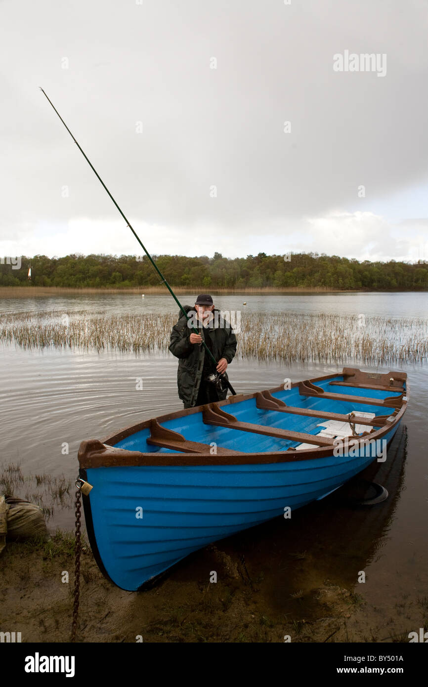 An angler prepares to go fishing in a loch in Western Ireland - Stock Image