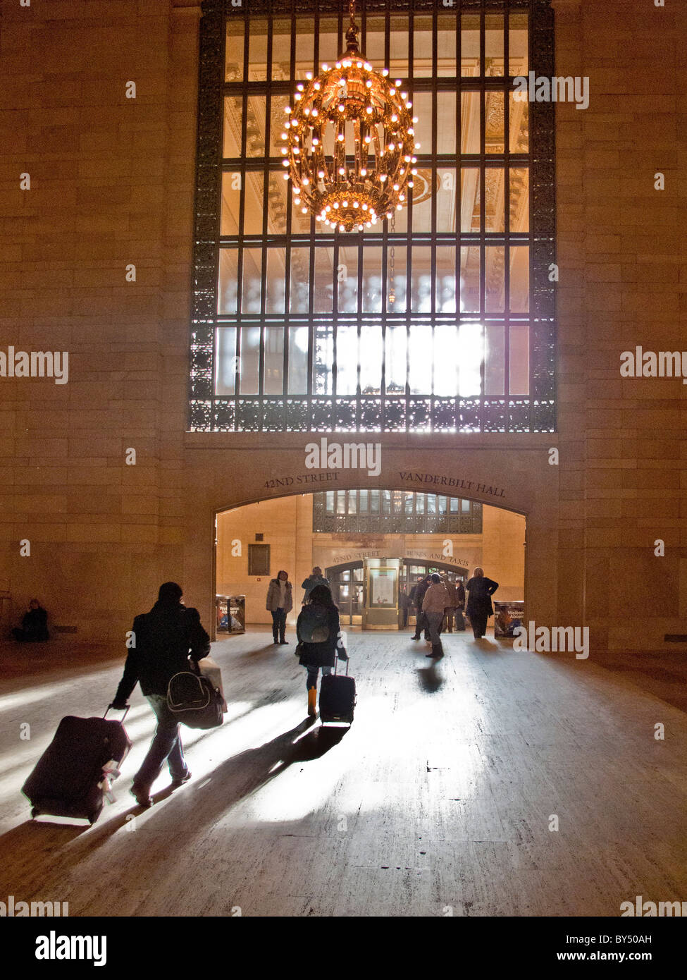 In afternoon sun, travelers with luggage head for the 42nd Street exit of Grand Central Station in midtown Manhattan, - Stock Image