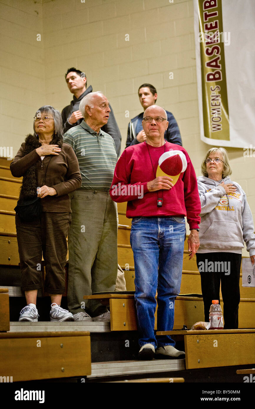 With one sour exception, students and staff make the Pledge of Allegiance  basketball game in a gymnasium in Southern - Stock Image