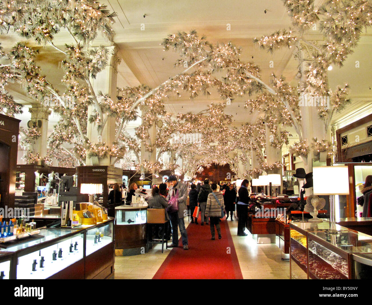 Indoor trees with electric lighted leaves decorate the Saks Fifth Avenue store at Christmas in New York City. - Stock Image