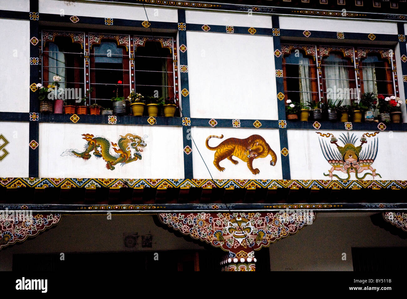 Colorful artwork in the typical Buddhist style adorns a traditional building in Paro, Bhutan - Stock Image