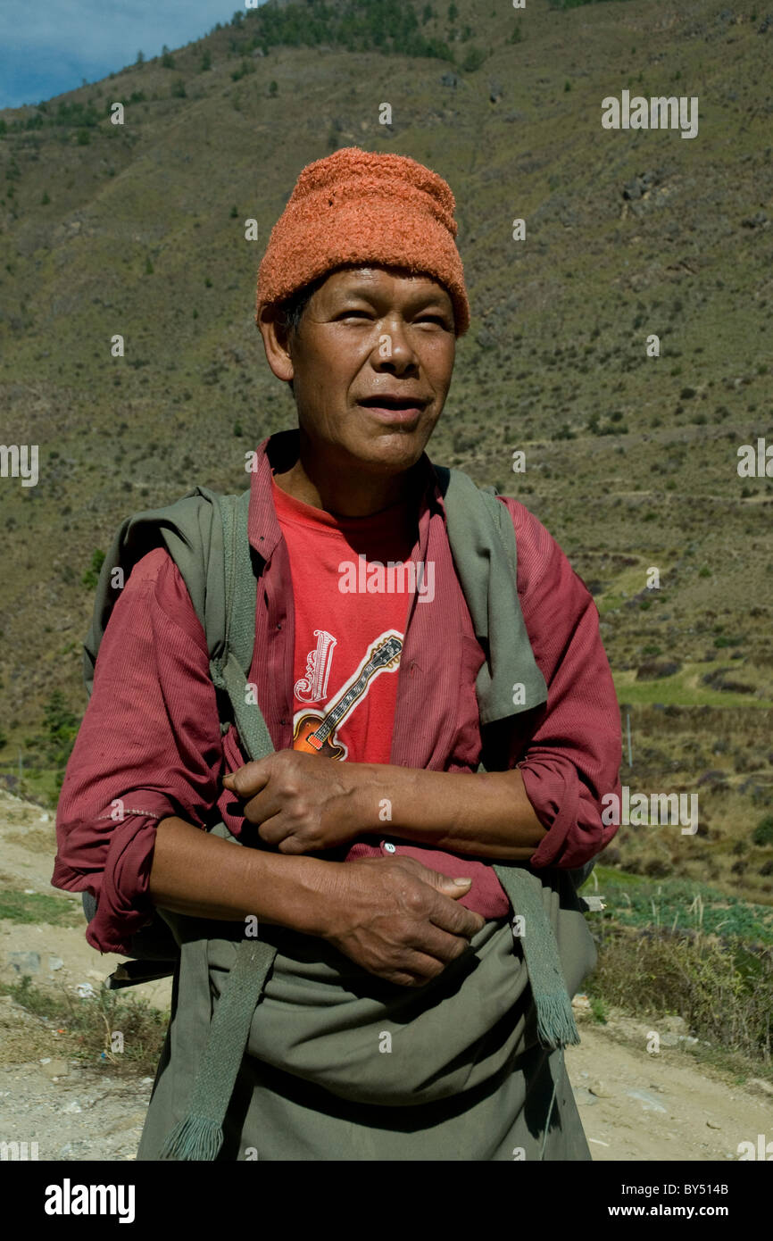 A Bhutanese farmer shows a cool modern style in the guitar adorning his tee-shirt - Stock Image