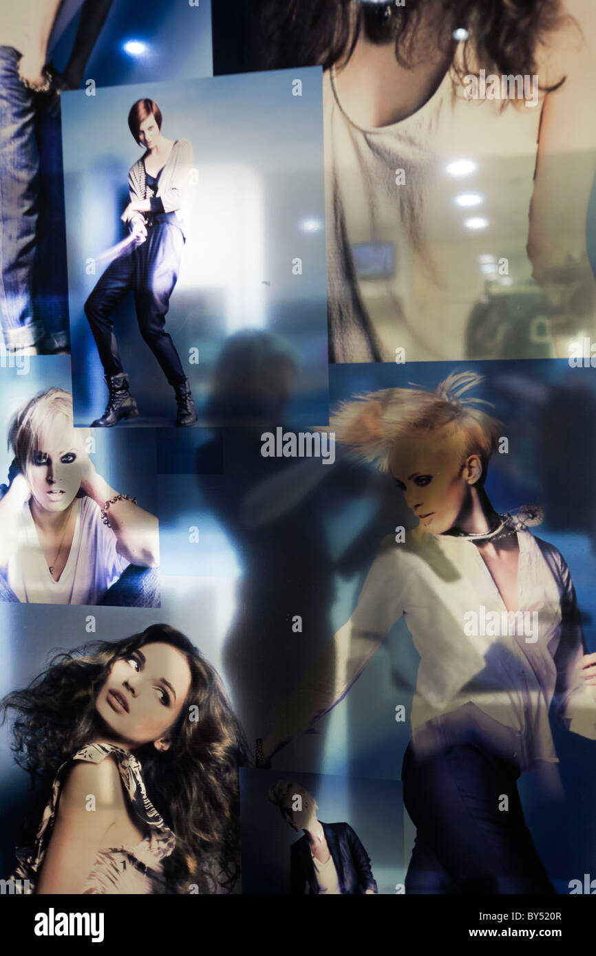 A woman hairdresser seemingly works on the graphics of glamorous models' hair in salon shop window. - Stock Image