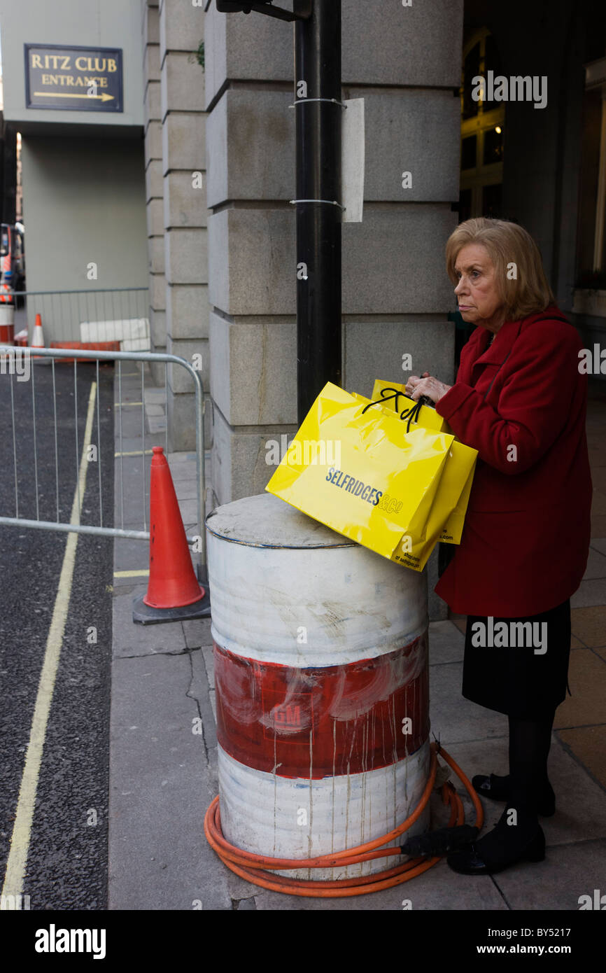 A lady with a Selfridges department store shopping bags stands by old construction oil drum outside Ritz roadworks. - Stock Image