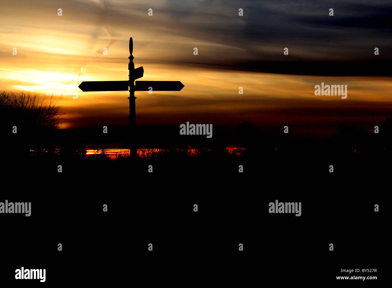 silhouetted crossroads signpost - Stock Image