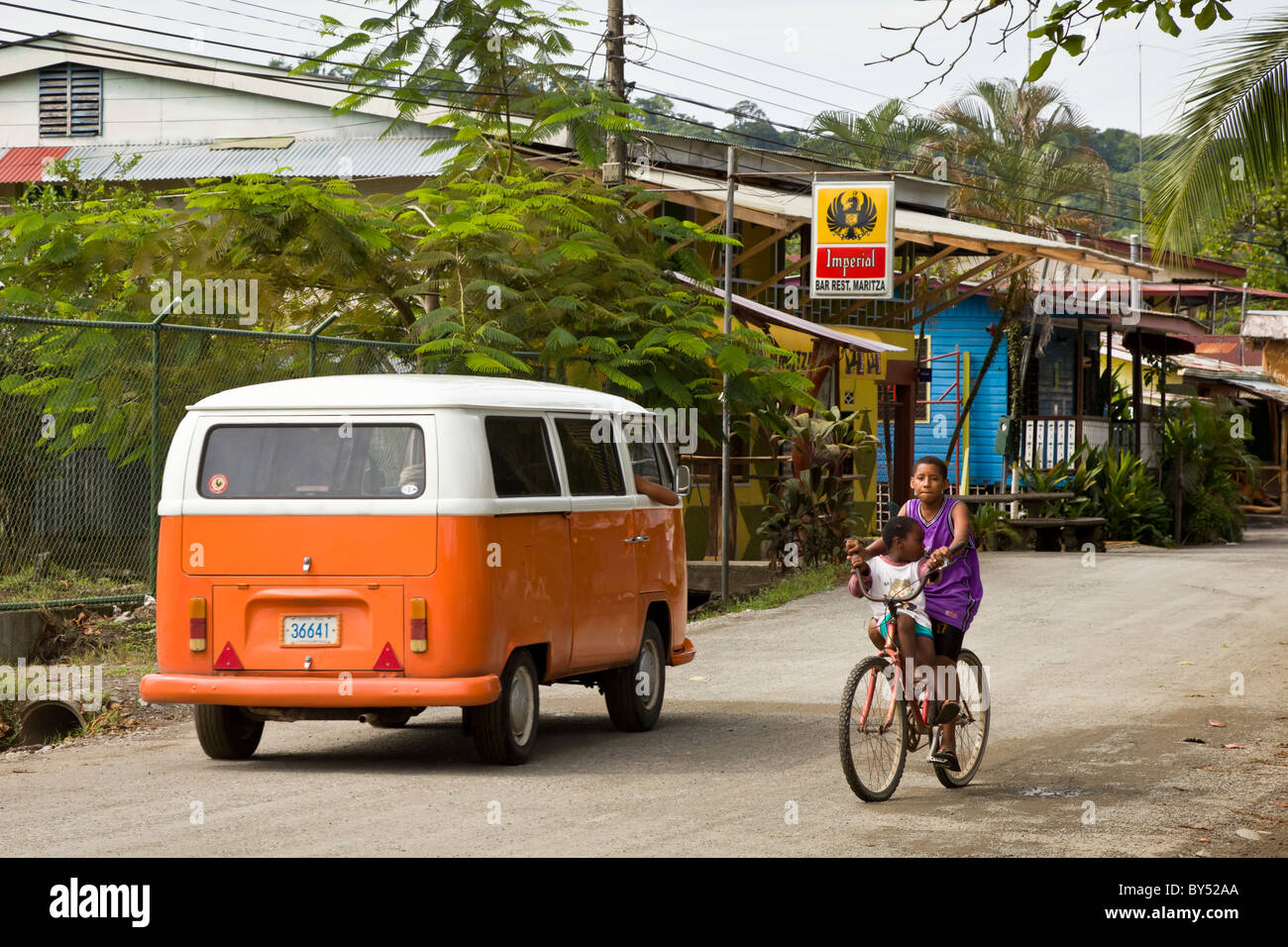 Two kids riding a bike on the street with an orange VW bus Puerto Viejo, Costa Rica. - Stock Image