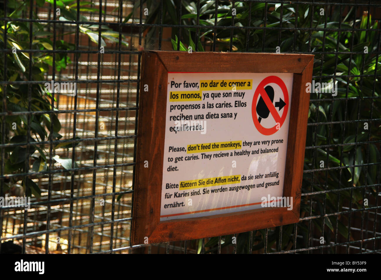 Don't feed the monkeys sign at zoo park - Stock Image