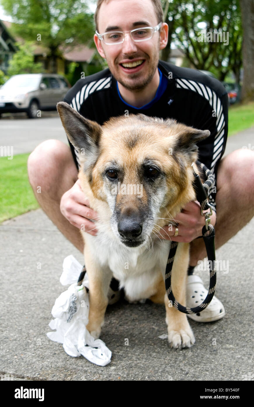 Man with his dog, a German Shepherd on the sidewalk with leash and doggy bag, Vancouver, British Columbia, Canada - Stock Image