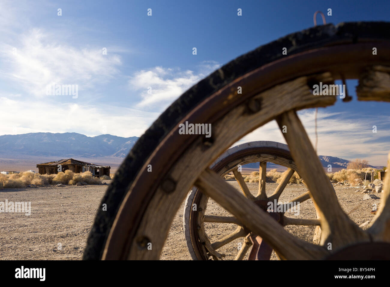 Ruins and wooden wagon wheels in Ballarat, a Death Valley ghost town that flourished from 1897 to 1905 in California, - Stock Image