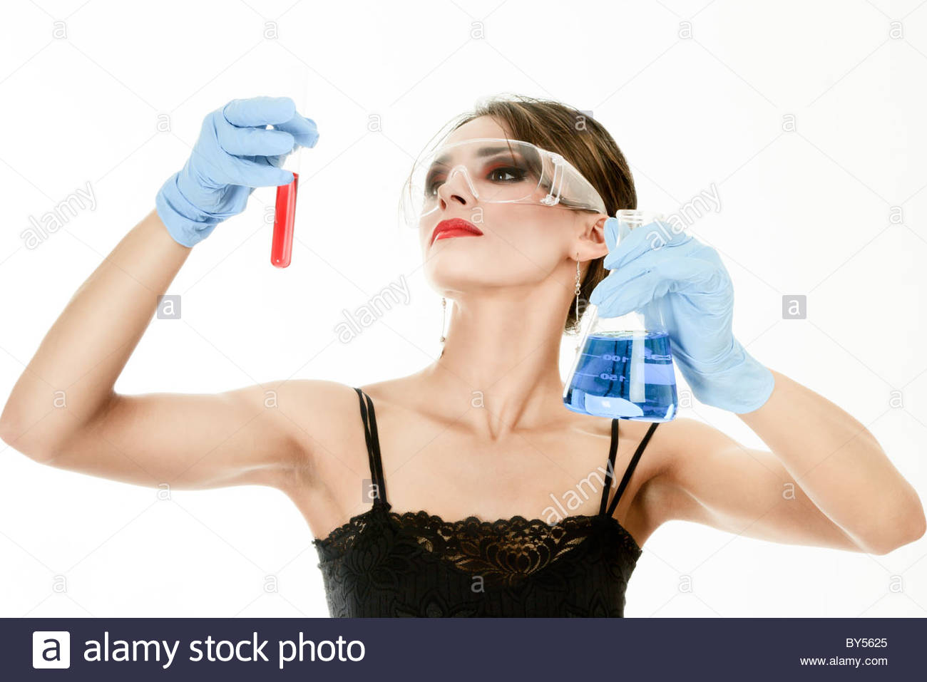 Young woman holding test tubes in hands during scientific experiment Stock Photo
