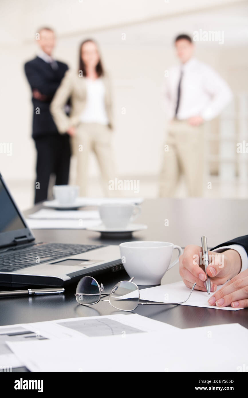 Vertical image of human hands making notes on paper on background of standing business people - Stock Image