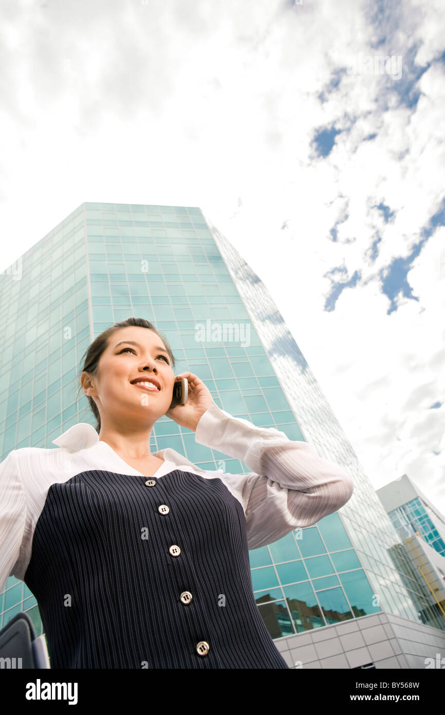 View from below of smart business woman speaking on cellular phone on background of modern building - Stock Image